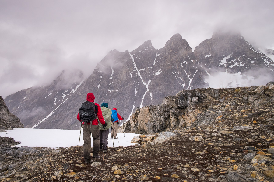 My trekking companions in full rain gear hiking through more snow with mountains in the background