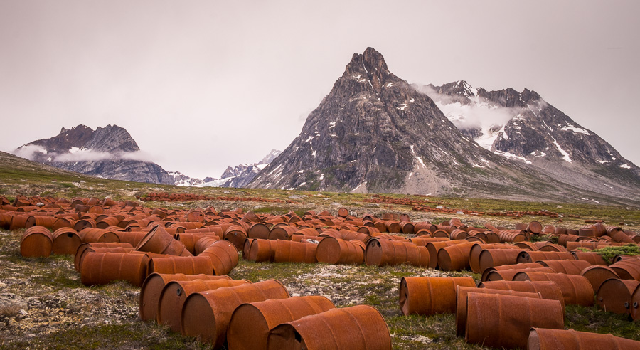 Hundreds of rusted fuel barrels in front of the mountains of East Greenland