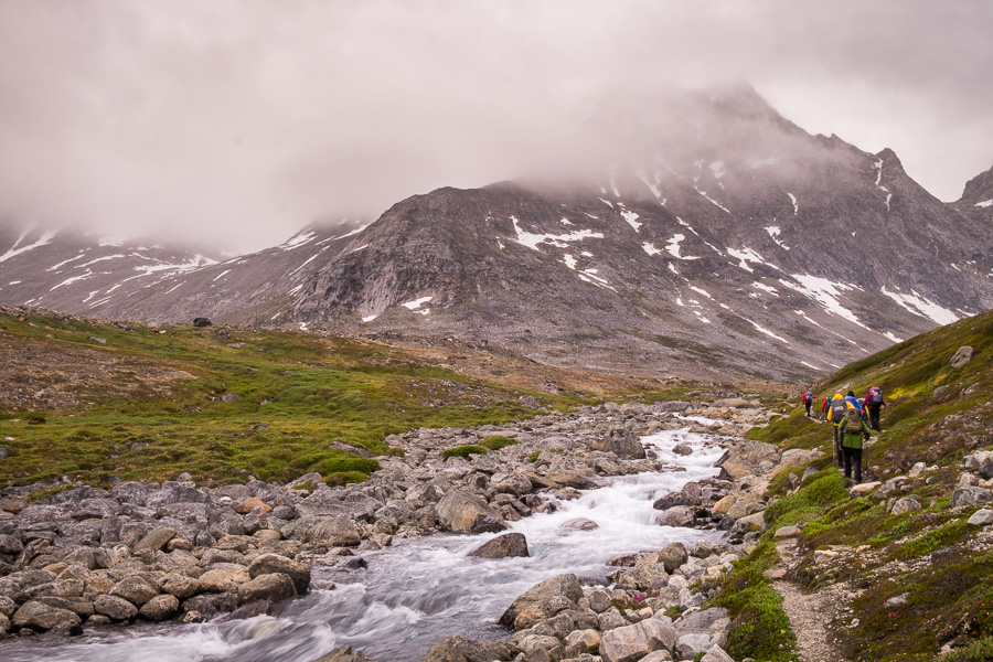 Trekking companions hiking beside a fast-flowing stream with fog-shrouded mountains in the background