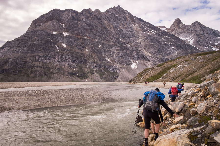 Trekking group picking their way along the rocks lining the river to avoid the water for as long as possible