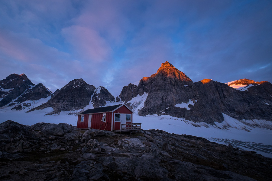 Sunset bathing the tips of the peaks behind the Tasiilaq Mountain Hut with a golden light. The hut is in the foreground