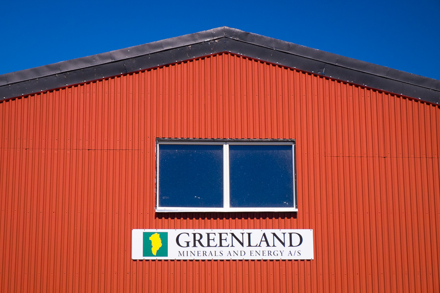 Red shed in Narsaq with a sign for Greenland Minerals and Energy and an outline of Greenland