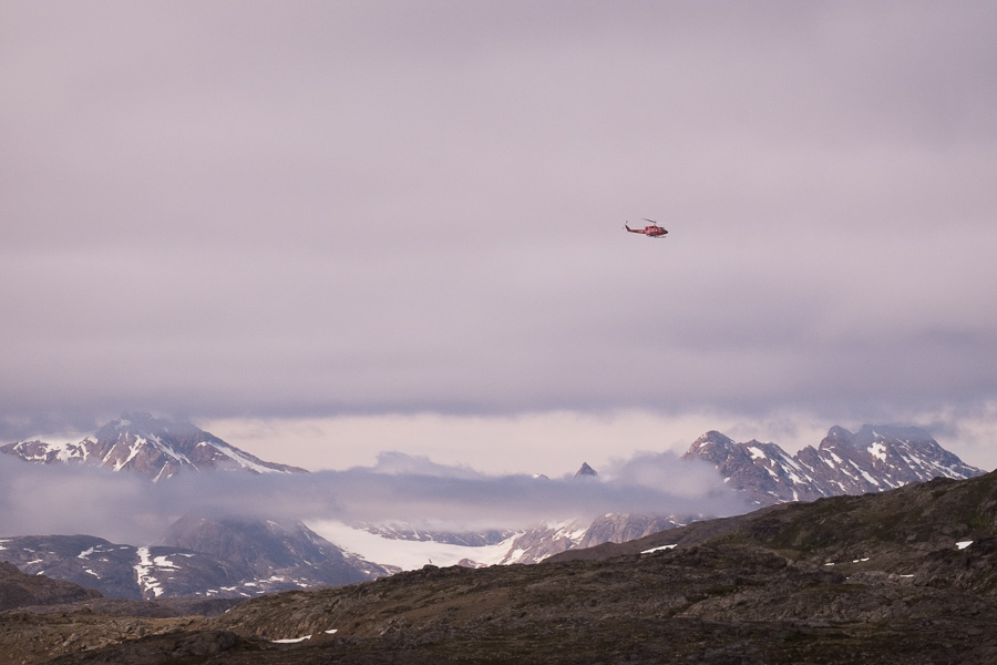 An Air Greenland helicopter flying below the low cloud to transfer passengers from Tasiilaq to Kulusuk in East Greenland