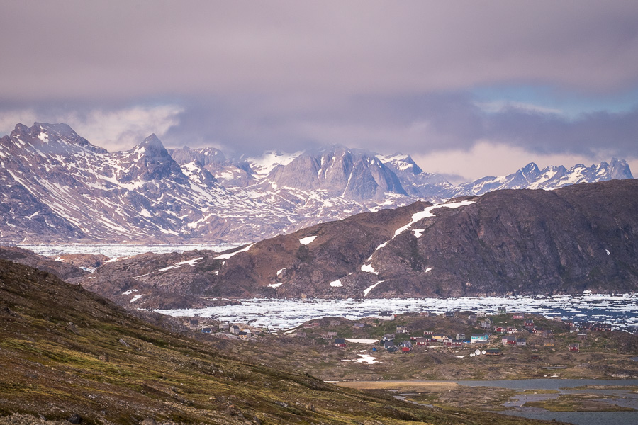The colourful houses of Kulusuk are dwarfed by the dramatic landscape. Seen while hiking from Kulusuk to Isikajia, East Greenland