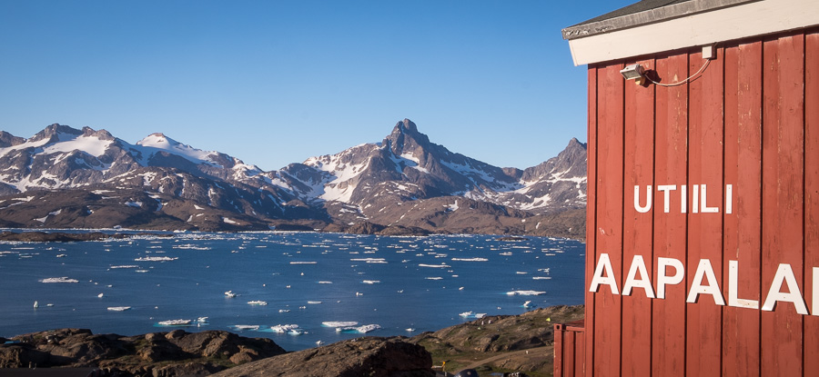 The edge of the Red House with its name in Greenlandic, overlooking the Tasiilaq Fjord - East Greenland