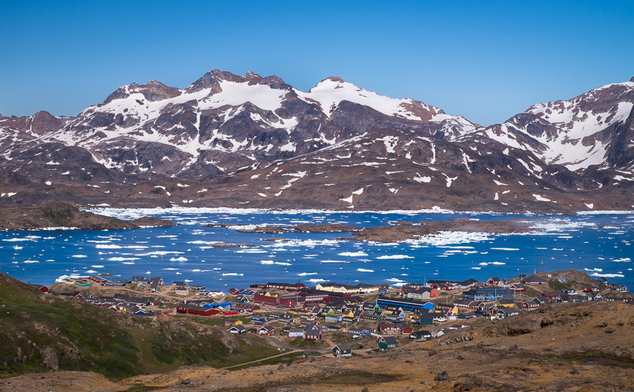 Looking down on the colourful buildings of Tasiilaq from a high vantage point, with the Tasiilaq Fjord and mountains in the background. East Greenland