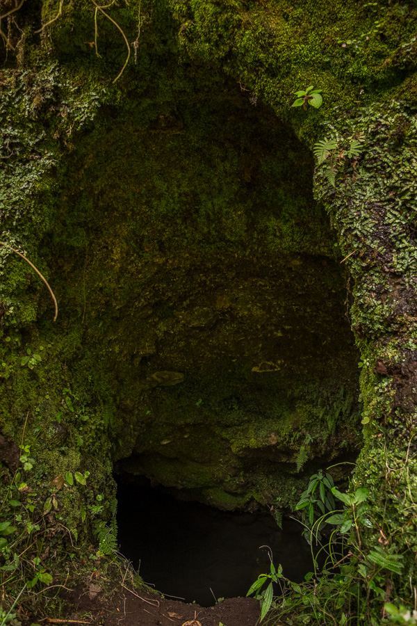 Hole in the rock revealing an underground river next to the hiking trail leading to the Cascada Condor Machay near Quito, Ecuador